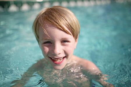 A happy little boy child is smiling and laughing as he swims in the pool on a sunny summer day. photo