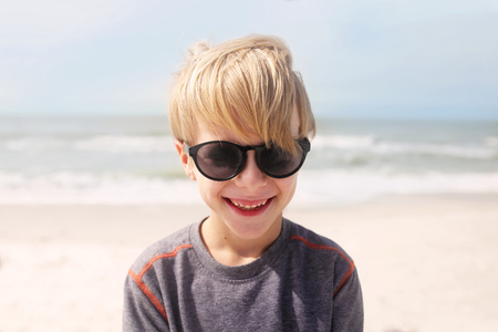 A happy, smiling little 7 year old boy is laughing as he stands on the beach by the ocean on a windy summer day. photo