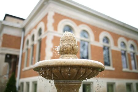 water town: A close up of water droplets spashing off of the pineapple top of an old tan, stone fountain, in front of a historic, small town building. Stock Photo