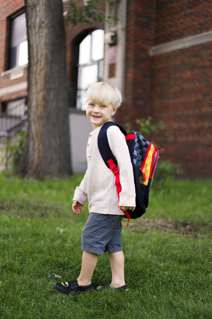 A happy little four year old boy is smiling as he wears his new backpack and walks to the old brick school building on his first day of preschool. Reklamní fotografie
