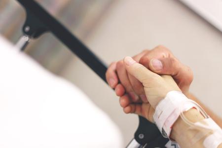 Die Hand einer Frau mit einem Krankenhaus Armband und IV hält die Hände mit ihrem Mann und beten vor der Operation. Standard-Bild - 82980461