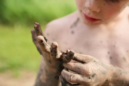 A little boy who has been playing outside in the summer, is picking mud off of his very dirty hands.  Shallow depth of field. Stock Photo
