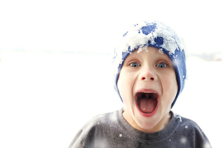 A super happy kid with a big smile is wearing an ice covered stocking cap as he plays outside in the winter snow, catching snowflakes. photo