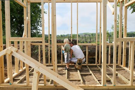 A father and his young son are working together to build the wooden frame walls for a backyard garden shed.