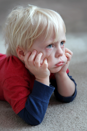 A bored and grumpy toddler child is laying on the carpet at home, pulling on his cheeks and making a pouting face. Stock Photo - 83006371