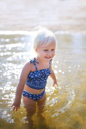 A happy little toddler child is smiling as she plays in the shallow water at the beach by the lake on a summer day.