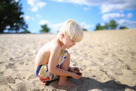 agachado: Un niño rubio lindo del muchacho del pelo es agachado abajo, buscando y recogiendo rocas y seashells en la playa en un día de verano.