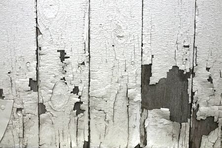 A textured background of peeling white paint on the wooden exterior wall of an old farm house. Stok Fotoğraf