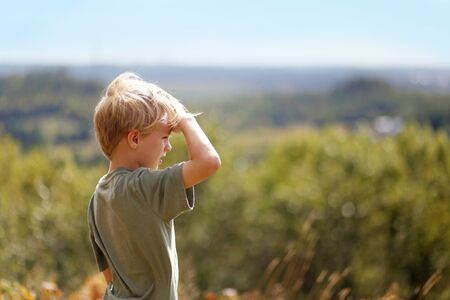 A little 8 year old boy out on a nature hike, is sheilding his eyes from the sun as he looks out over the trees while high up on a bluff.