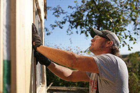 Un giovane coperto di segatura indossa occhiali di sicurezza e ha un chiodo in bocca mentre sta installando una finestra in una tettoia che sta costruendo. Archivio Fotografico - 91254477