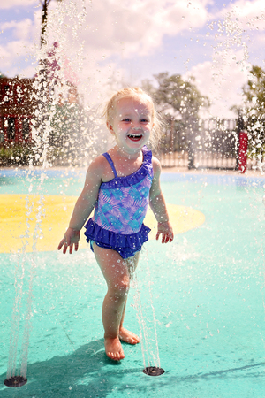 a cute, happy, 2 year old toddler girl is laughing as she gets wet playing in the water as a splash park outside on a summer day.