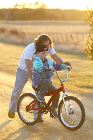 A father is helping his young child learn to ride his bike on a sunny spring evening. Stock Photo