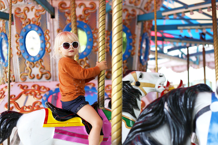 A cute llittle toddler girl in big fashionable sunglasses is riding on a classic carousal horse at a small town carnival. Stock Photo