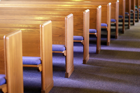 Window light is shing on rows of empty church pews in a Church Sanctuary without any people in it.