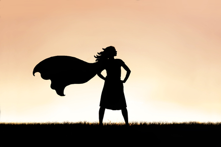 The silhouette of a strong, beautiful caped super hero woman stands isolated against a sunset in the sky background.