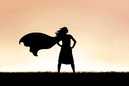 Het silhouet van een sterke, mooie superheld-vrouw met caped staat geïsoleerd tegen een zonsondergang aan de hemelachtergrond.