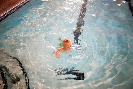 A young boy child is swimming in the water in an indoor hotel pool while on family vacation. 版權商用圖片