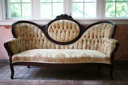 A vintage victorian high cameo back floral sofa with dark carved Mahogany woodwork sits in a sunroom of an old home.