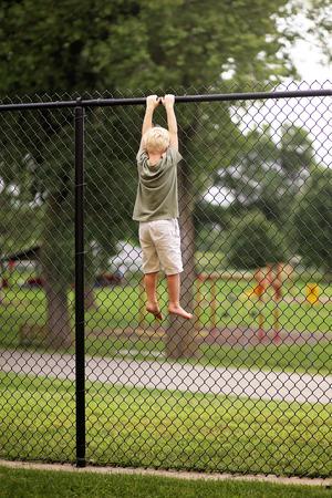 Un niño pequeño estaba tratando de trepar por una cerca de tela metálica alta para escapar a un patio de juegos, pero está atascado colgando de sus manos en la parte superior.