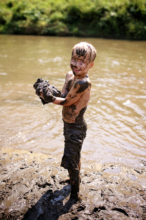 A happy young boy child is covered in mud as he laughs, swims, and plays outside in the river on a summer day. Reklamní fotografie