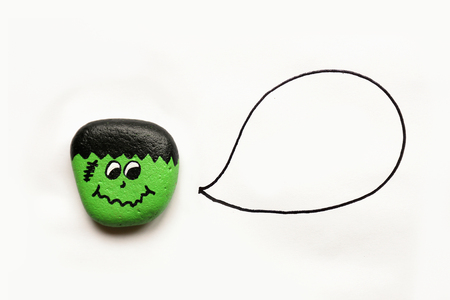 A cartoon painted Halloween Monster rock is isolated on a white background with a speech bubble that is empty.