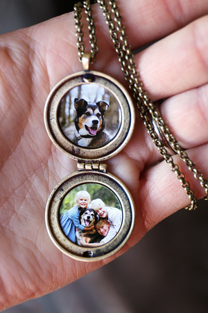 A womans hand is holding an open gold antique locket and chain with pictures of children and a pet dog inside.