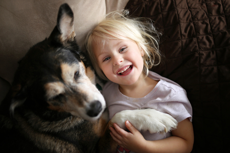 A happy, smiling little girl child is hugging her pet dog as they snuggle at home on the couch. Фото со стока