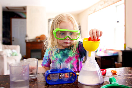 A little girl child is at home doing a science experiment with a toy science kit. Imagens