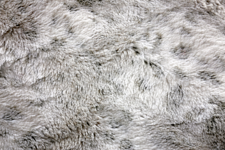 Close up on a background of soft and fuzzy, white and grey, shag faux fur blanket material.