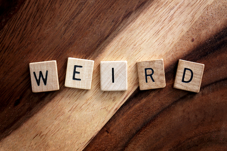 The Word Weird is spelled out in wooden letter blocks on a dark wood grain background.