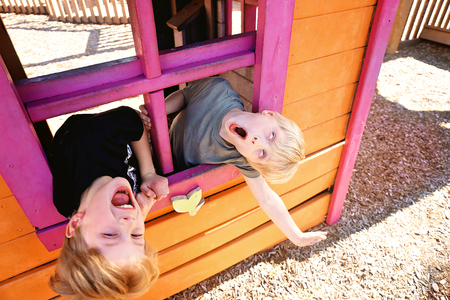 Two cute little kids are making funny faces as they play outside in a clubhouse at a playground.