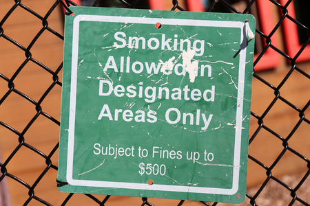 A green sign is hung on a chain link fence at a playground, and says Smoking allowed in designated areas only, $500 fine. Stock Photo