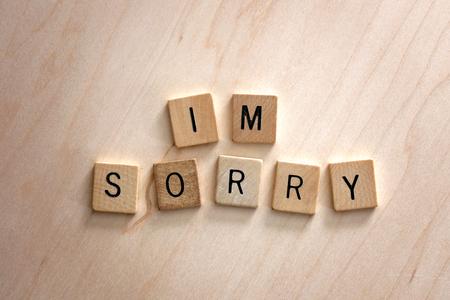 """Las palabras """"lo siento"""" están escritas en bloques de letras de madera sobre un fondo de madera. Foto de archivo"""
