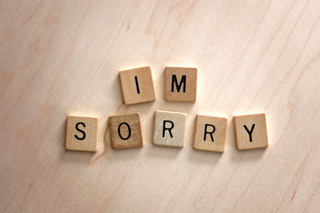 "The words ""I'm Sorry"" are spelled out in wooden letter blocks on a wood background."
