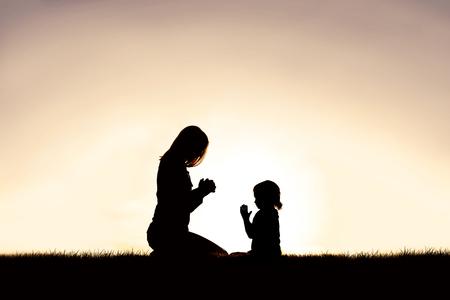 Una silueta de una madre cristiana que enseña a su hijo pequeño a orar mientras se sientan pacíficamente afuera, contra la puesta de sol en el cielo. Foto de archivo
