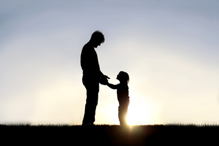 A silhouette of a father and his happy little child are holding hands and smiling at each other as they play outside at sunset.