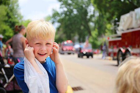 Un niño lindo y feliz se cubre los oídos de las fuertes sirenas de los camiones de bomberos en un desfile estadounidense de una pequeña ciudad. Foto de archivo