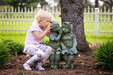 A cute little girl is sitting on a bench, whispering a secret as she plays with two little garden statue friends. 版權商用圖片