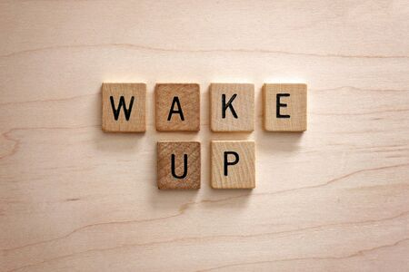 The words wake up are spelled out in square wood letter tiles on a light wooden background.