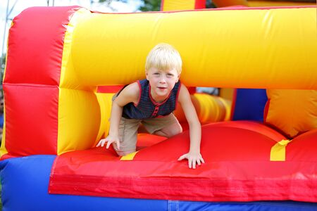 A cute little kid is playing on an inflatable bounce house obstacle course at a Small town American festival.