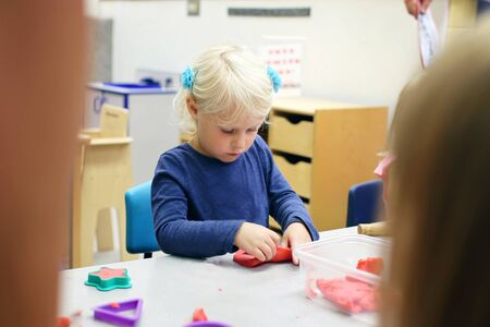 A little preschool aged girl child is playing with sculpting clay at school. Reklamní fotografie