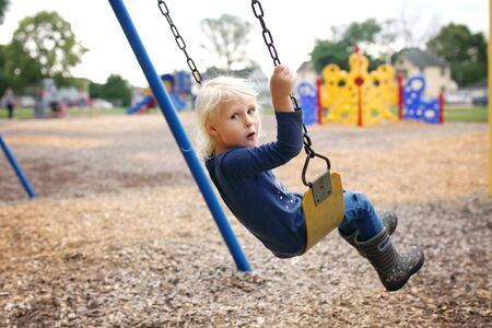A cute little preschool girl child is swinging at the elementary school playground.