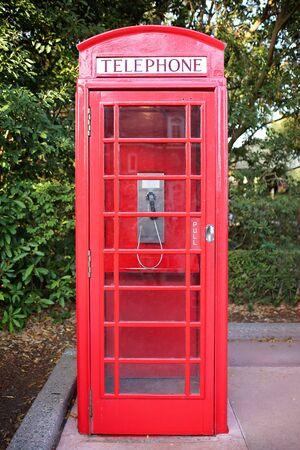 An old fashioned British style red painted telephone booth box sits on a sidewalk.