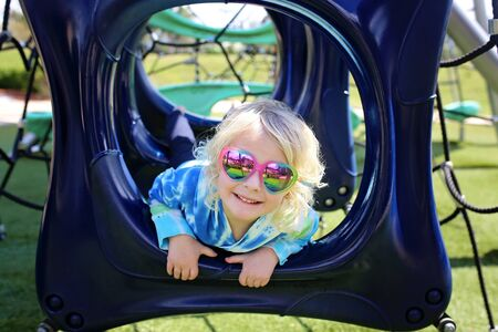 A cute little 5 year old girl is wearing heart shaped sunglasses and smiling as she plays at the playground in the park on a summer day.