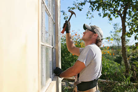 A young carpenter man is using a hammer as he builds the trim around a newly constructed garden shed.