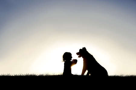 A silhouette of a sweet little girl child sitting outside with her friendly family pet dog.