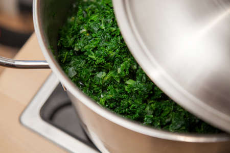 Typical German green kale in a cooking pot at domestic kitchen