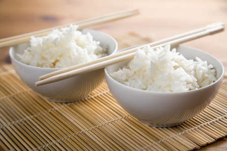 Two bowls of basmati white rice with wooden chopsticks