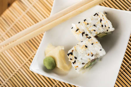 Two salmon avocado inside California sushi rolls with wasabi, pickled ginger and wooden chopsticks