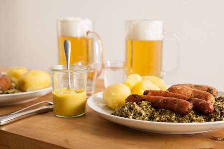 Oldenburger Grünkohl mit Wurstmischung, Salzkartoffeln, Senf, Bier und Getreide Standard-Bild